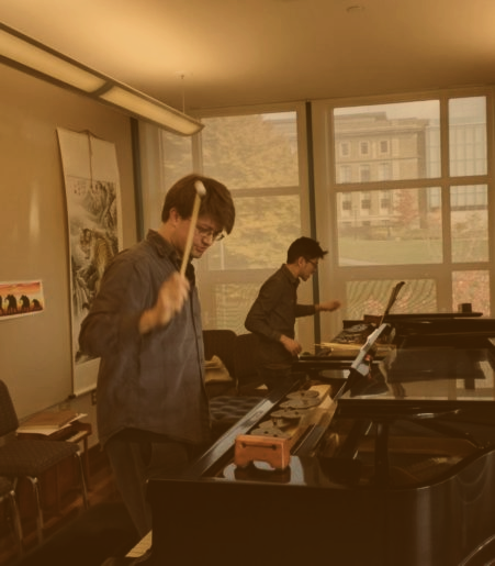 Photo of two pianists rehearsing at two pianos. Each is holding a mallet midair about to strike a woodblock on the piano desk.