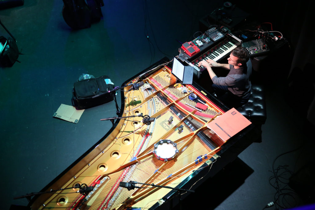 Overhead shot of a pianist playing on digital keyboard perpendiculat to grand piano