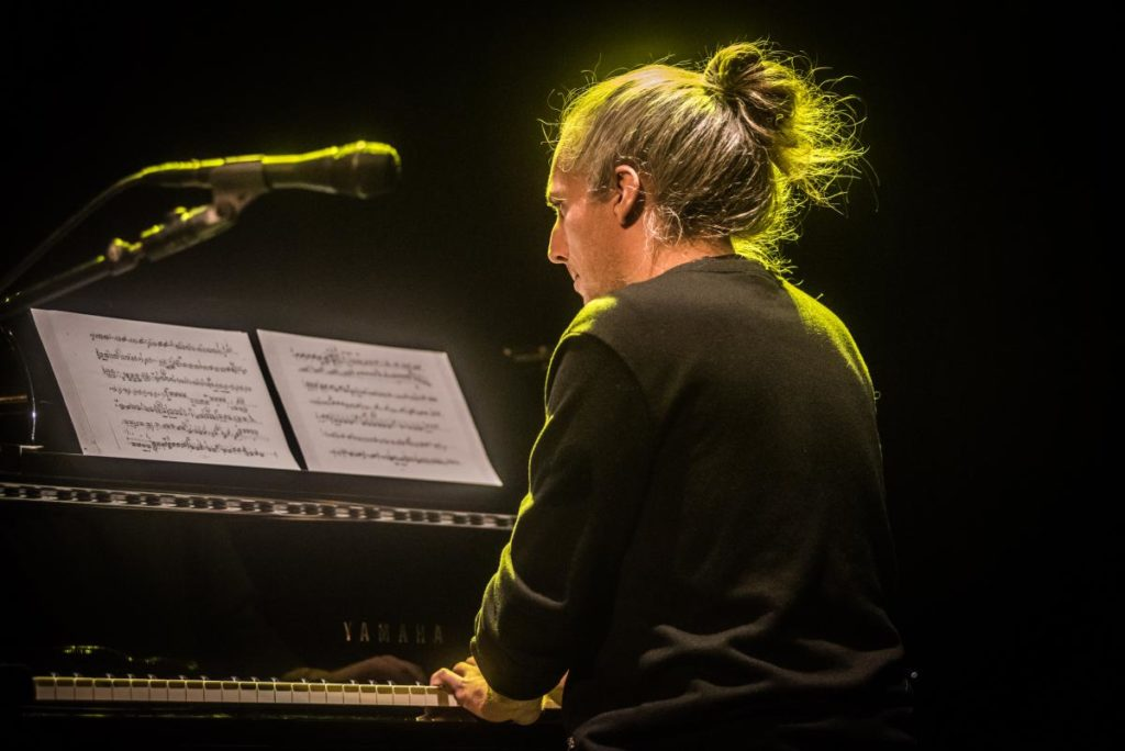 Photo of male pianist with hair in bun mid-performance concentration