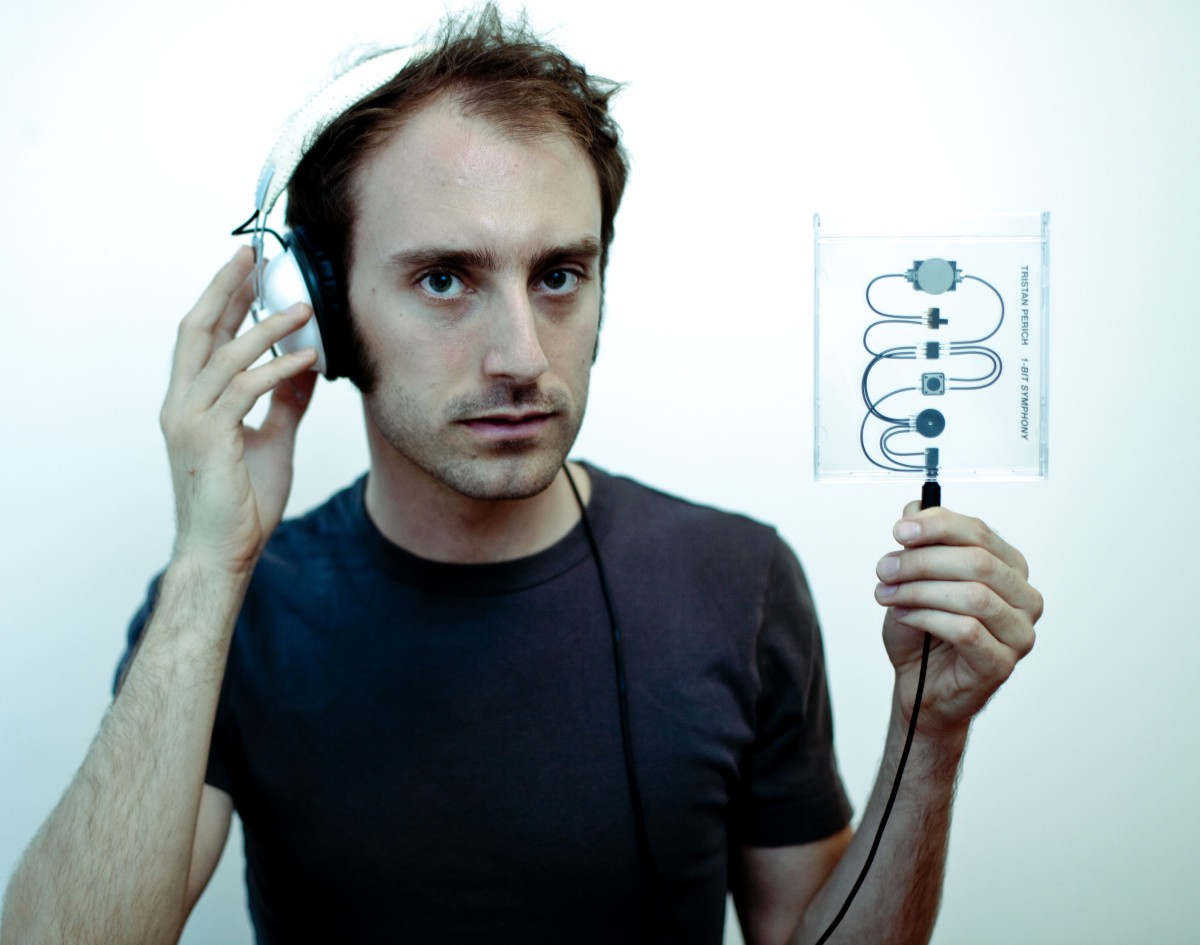Photo of Tristan Preich with headphones holding up one of his one-bit instruments