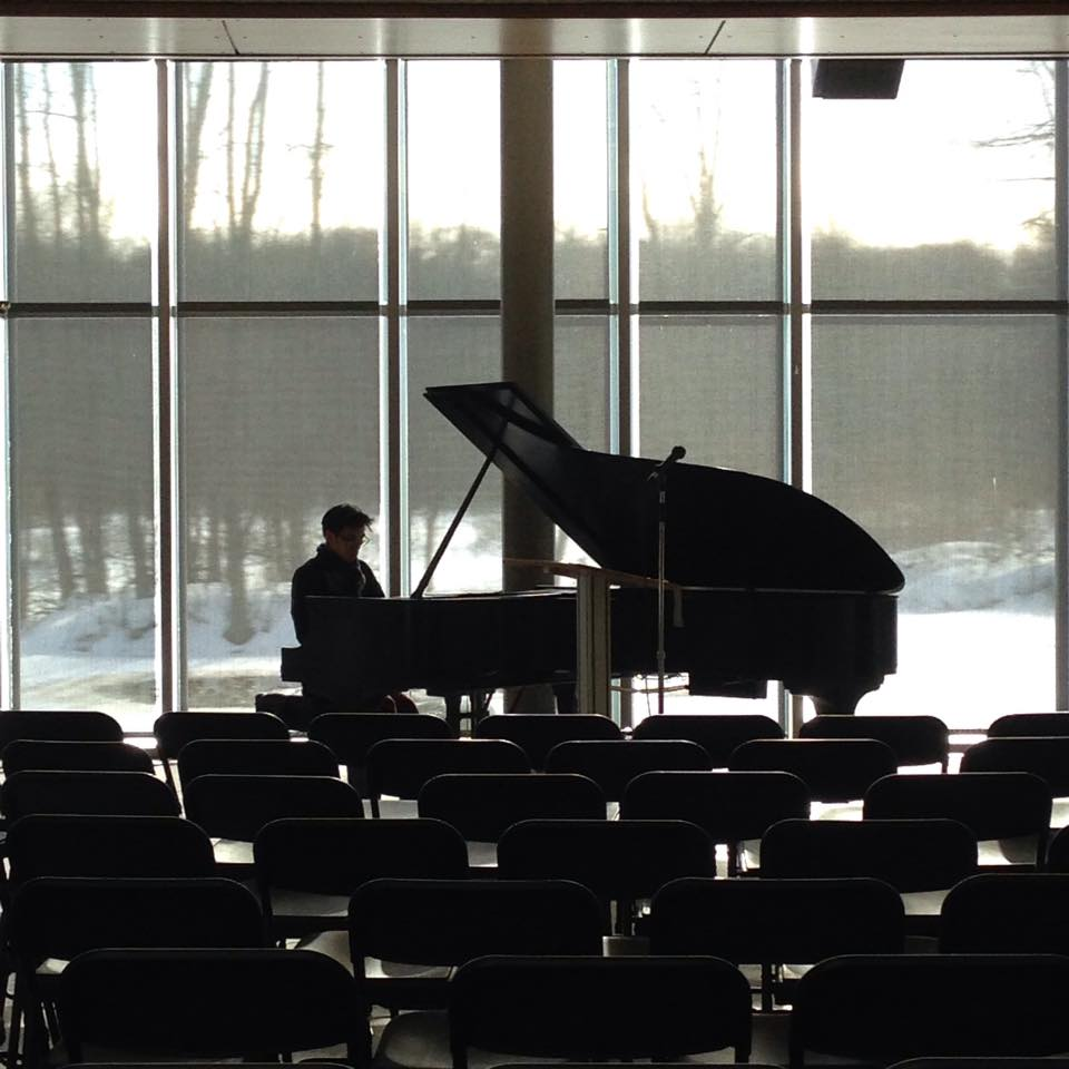 Moody photo of pianist playing against a snowy backdrop, visible through large windows, at the Lab of Ornithology